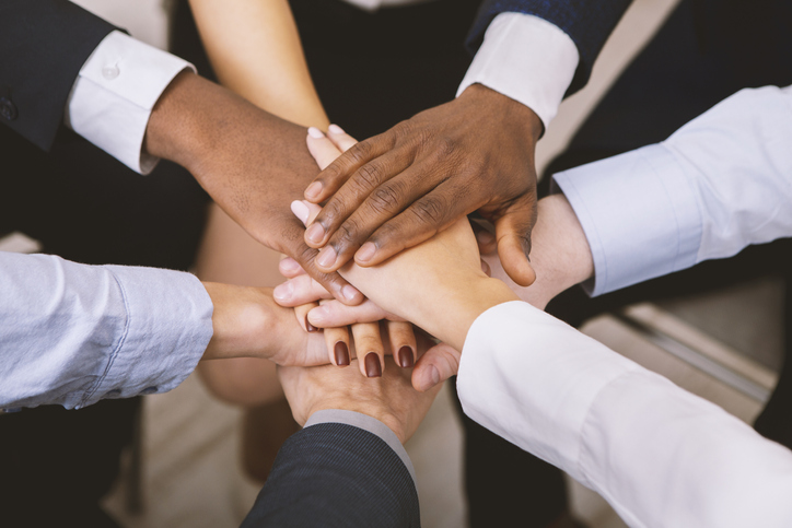 Stacked hands of people of different ethnicities standing in a circle