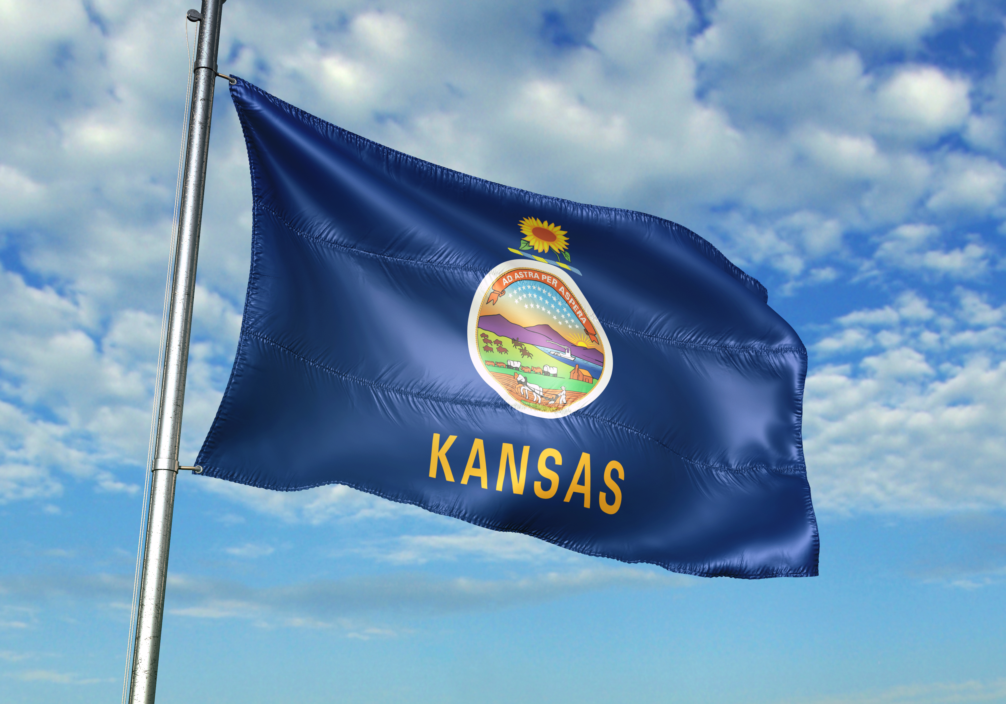 Kansas flag fluttering against a blue sky dotted with white clouds on a sunny day